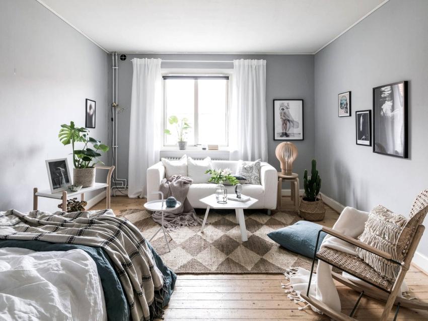 Спальня-гостиная в скандинавском стиле оформляется в светлой палитре