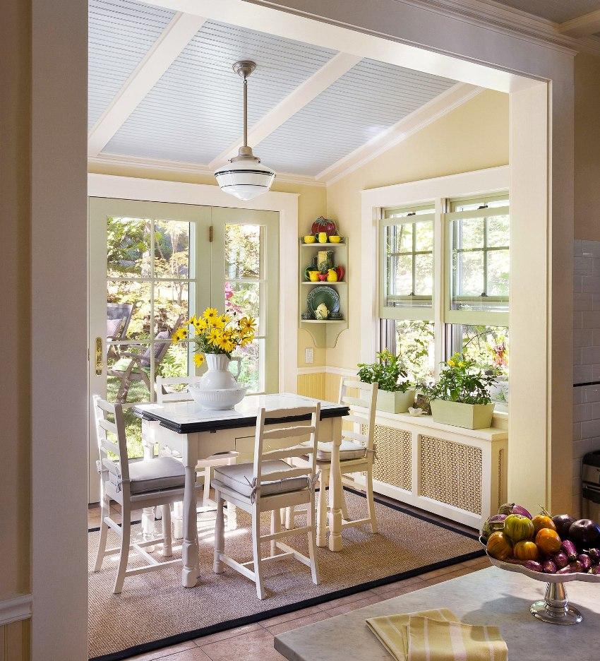 На окно кухни, оформленное без штор, можно разместить вазоны с цветами