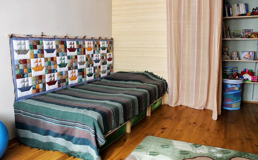 Проблему затирания стены в зоне спального места можно решить одним способом – повесить детский ковер на стену