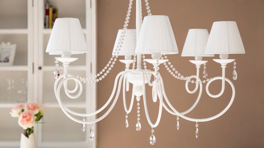 Некоторые дизайнеры предлагают делать люстру в классическом интерьере акцентным элементом комнаты