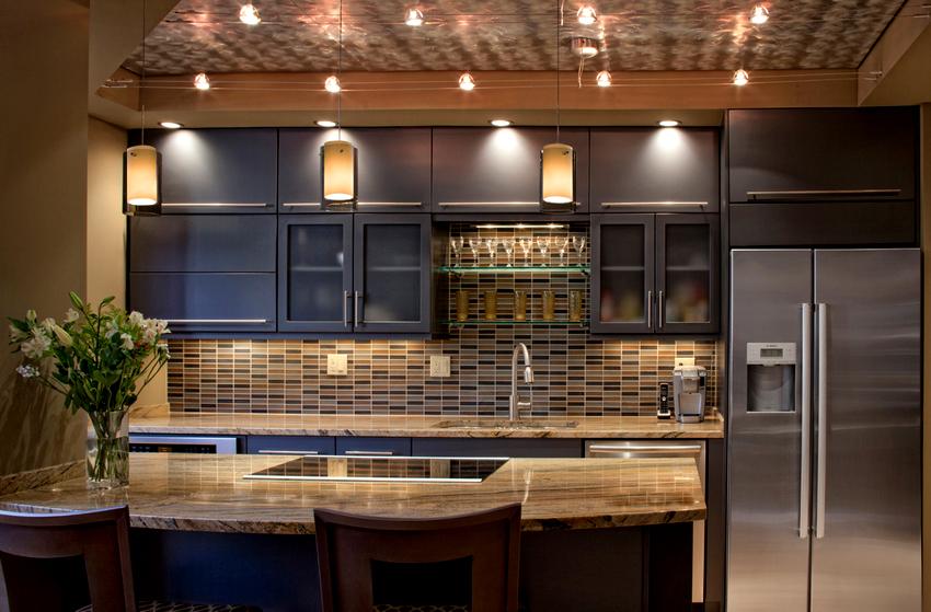В случае расположения светильников вдоль линии кухонного гарнитура на потолке появится возможность обеспечить освещенность узкой части столешницы