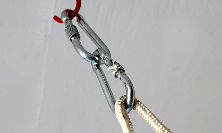 Чтобы смонтировать подвесное детское кресло, на крюк закреплённый к потолку устанавливается сначала один, а на него второй стальной карабин