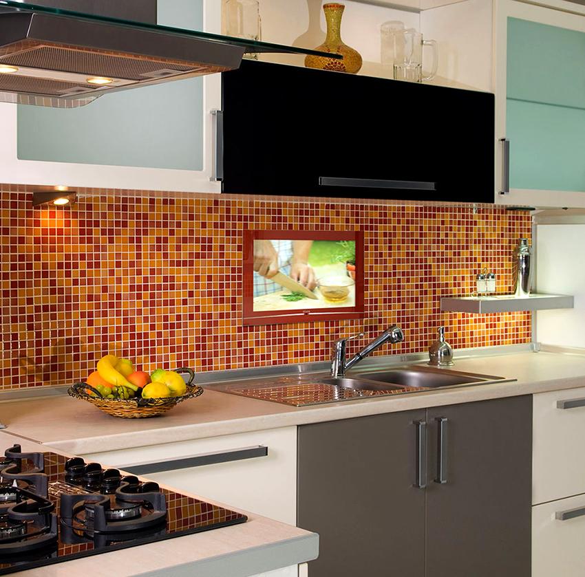 Интересный вариант размещения – это встраивание телевизора за кухонным стеклянным фартуком