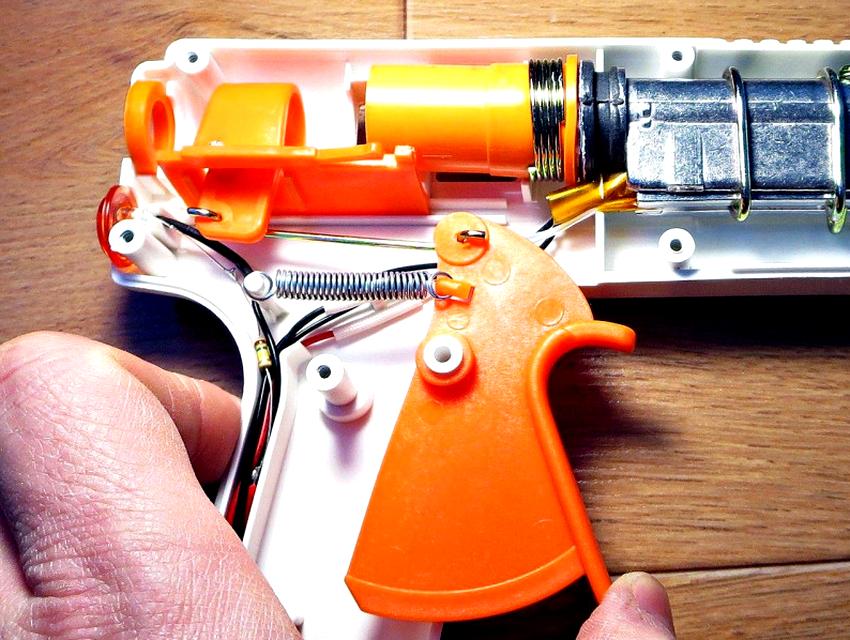 Клеевой пистолет состоит из втулки толкателя с курком, трубчатого приёмника и камеры нагрева