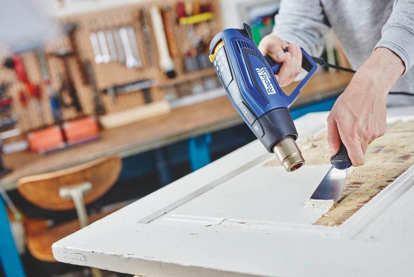 Процесс снятия старой краски с двери с помощью строительного фена