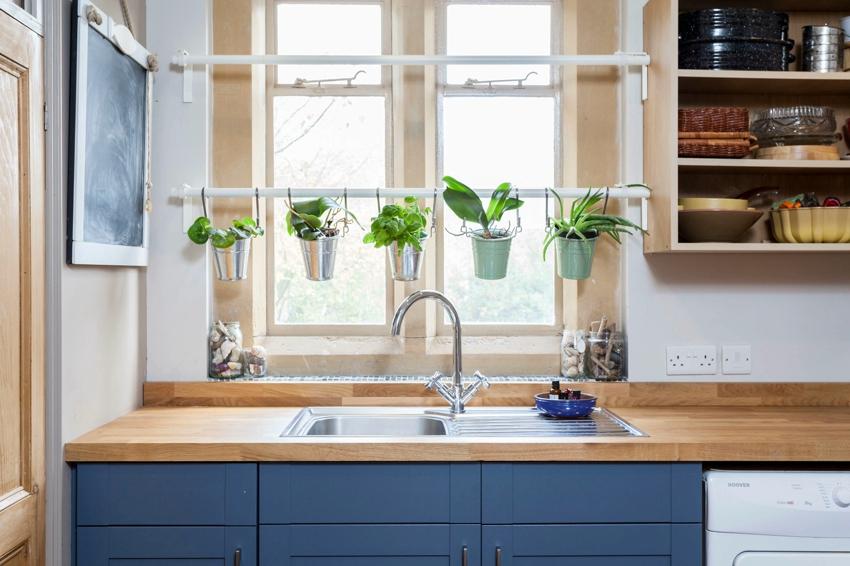 Возле окна на кухне размещена мойка и зона для выращивания цветов